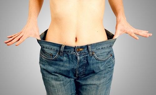 Jeune femme dans un jean trop grand après un régime réussi