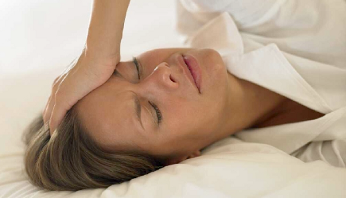 Frau im Bett hat nachts Kopfschmerzen