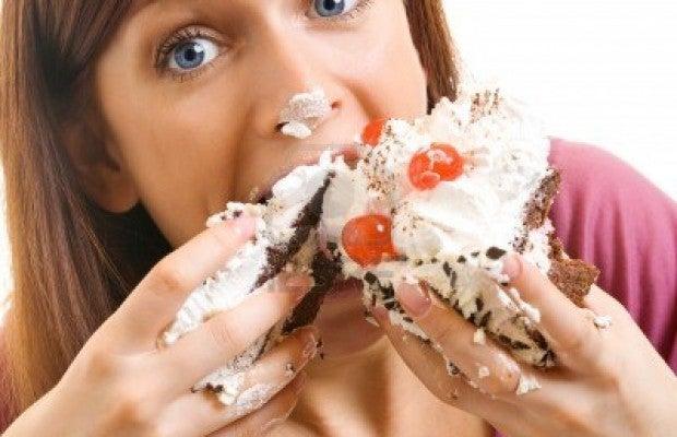 15025663-fröhliche-Frauch-die-Kuchen-isst-mit-einem-weißen-Hintergrund620x4001