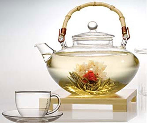 Weißer Tee in Teekanne mit Teeblüten