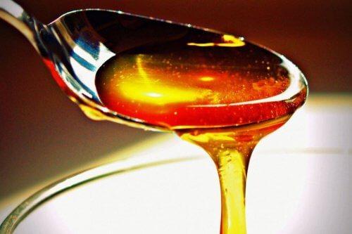 Honig fließt von einem Löffel
