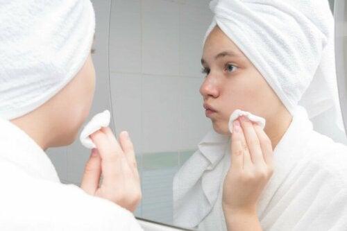 Gesichtsreinigung mit Apfelessig - Frau vor dem Spiegel