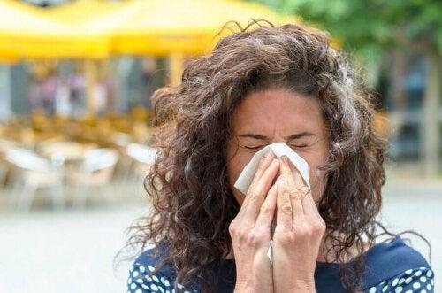 allergischer Schnupfen - Frau putzt sich die Nase