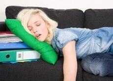 Junge Frau schläft faul auf einer schwarzen Couch