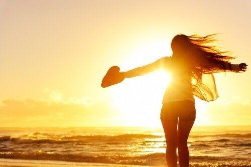Frau genießt das Meer mit ausgebreiteten Armen und sucht ihren Weg