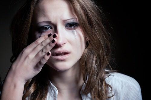 Junge Frau weint und wischt sich Tränen aus dem Gesicht