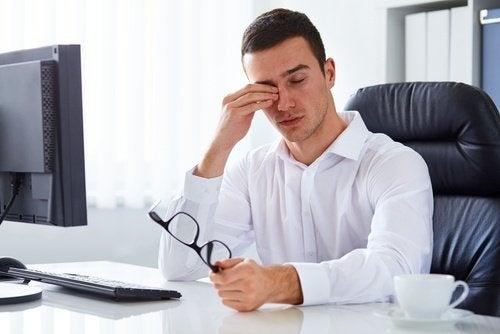 Mann sitzt müde vor Computer