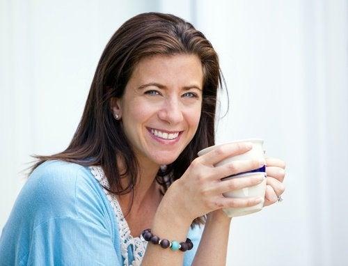 Frau mittleren Alters mit schönem Körper trinkt Tasse Tee