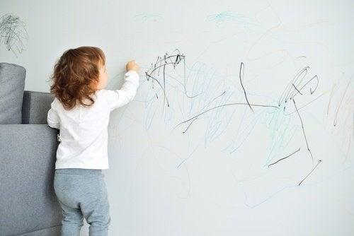 Kind bemalt eine Wand die Mama mit Zahnpasta putzt