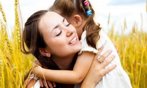 Mutter umarmt ihr Kind und denkt über Erziehung nach