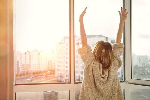 Frau streckt sich vor einem Fenster und wartet auf Veränderungen