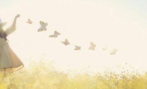 Kind mit Schmetterlingen als Symbol für Freiheit