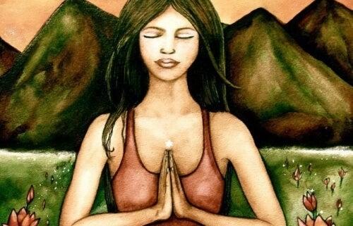 Frau betet vor einem Berg