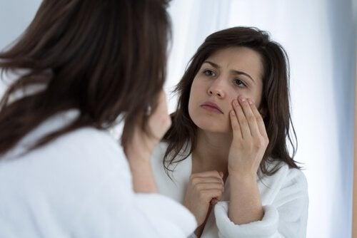 Frau schaut im Spiegel ihr Gesicht an und macht Löffelmassage