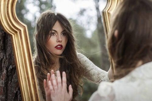 Frau betrachtet emotionalen Schaden im Spiegel