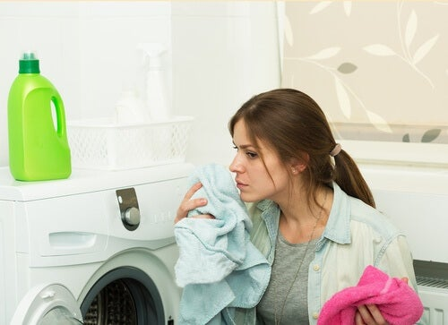 Frau wäscht Wäsce und verwendet Weichspüler