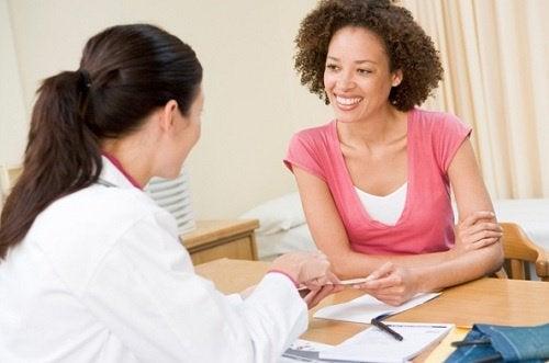 Frau beim Arzt spricht über Muskelkrämpfe