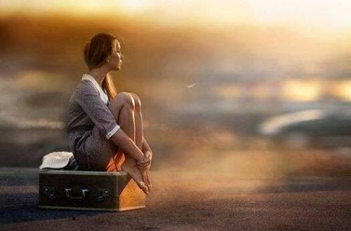 Frau sitzt auf einem Koffer und denkt über Entscheidungen nach