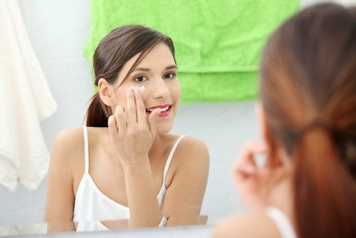 frau-schaut-in-den-spiegel-und-entfernt-make-up