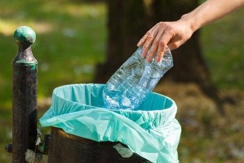frau-wirft-plastikflasche-in-den-muell-plastik