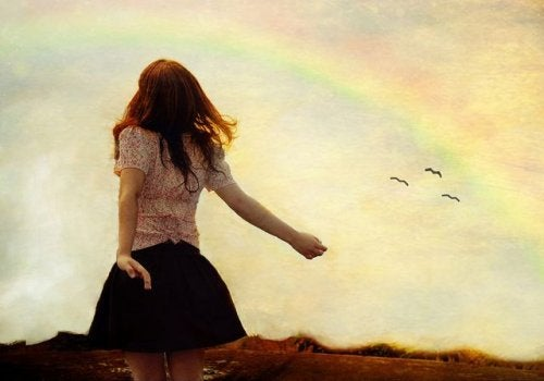 frau-schaut-in-den-himmel-mit-regenbogen-genehmigungen