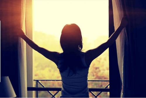 Frau am Fenster vertreibt Müdigkeit