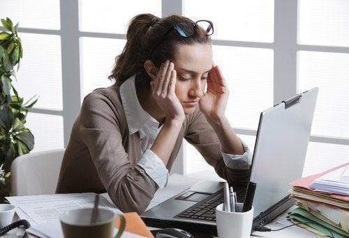 Frau am Computer hat Kopfschmerzen