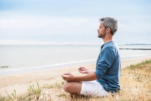 Mann meditiert am Strand und hat Ideen