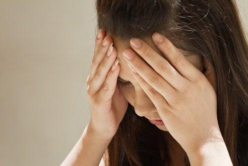 Frau mit Kopfschmerzen nimmt Knoblauch und Honig