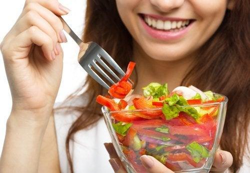 Frau mit Salat, der den Stoffwechsel anregt