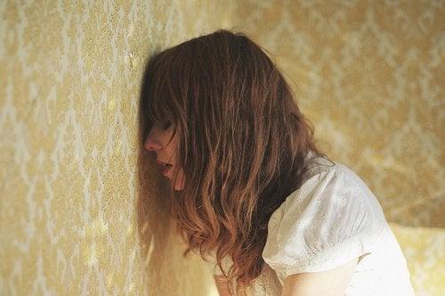 Frau lehnt Stirn an die Wand Menstruation