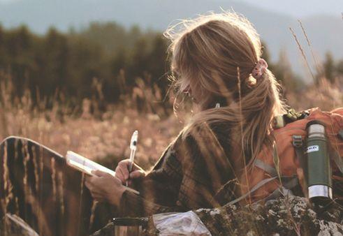 Frau schreibt Brief in freier Natur und möchte Selbstbild verbessern
