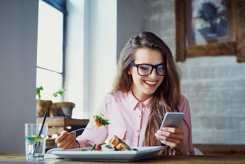 junge Frau essend und mit Handy