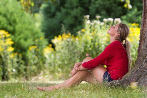 Frau sitzt unter einem Baum gehen