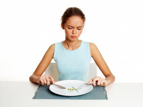 Frau vor leerem Teller denkt über Angewohnheiten nach