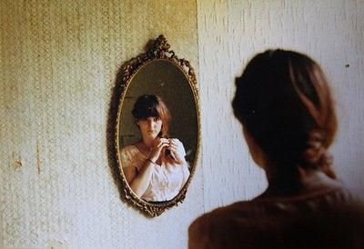 Frau blickt in den Spiegel und denkt über ihre Beziehung nach