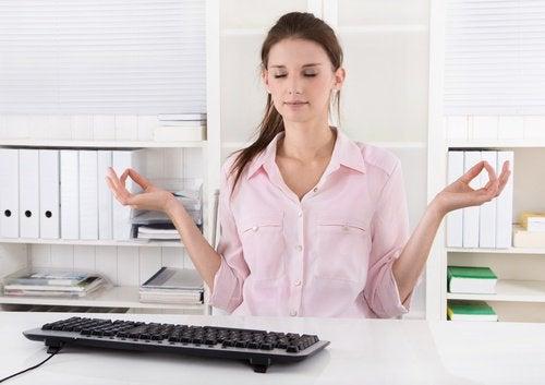 Frau meditiert am Schreibtisch