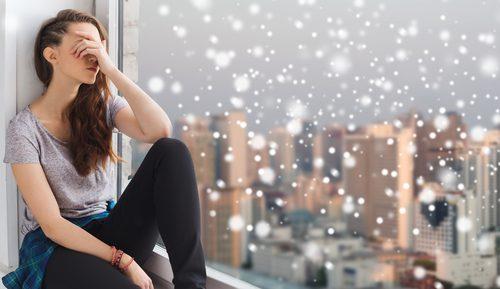 Frau sitzt am Fenster Depression