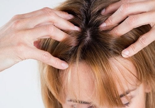Frau macht Kopfmassage gegen Kopfschmerzen