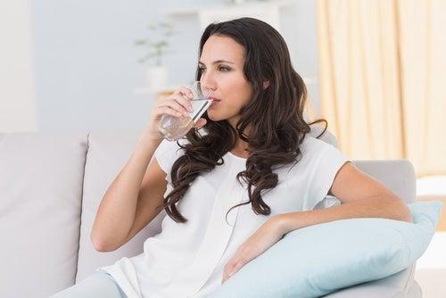 Frau trinkt Wasser gegen Müdigkeit