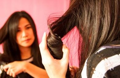 Frau verwendet Glätteisen doch damit wird ihr Haar nicht jung bleiben
