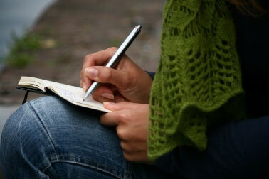 Frau schreibt ein Tagebuch, um ihre Resilienz im Alltag zu fördern