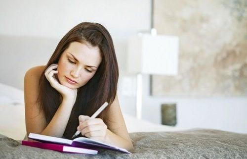 Frau schreibt Tagebuch und möchte Angst und Nervosität lindern