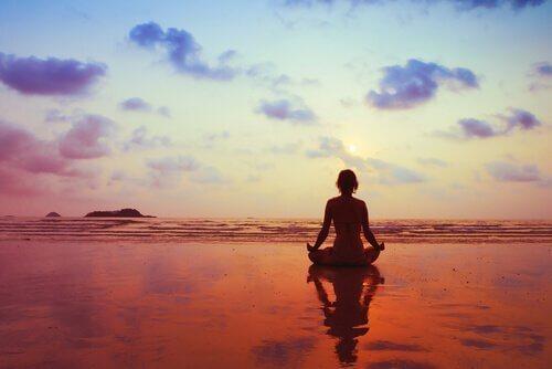 Frau meditiert am Meer im Abendrot und möchte Angst und Nervosität lindern