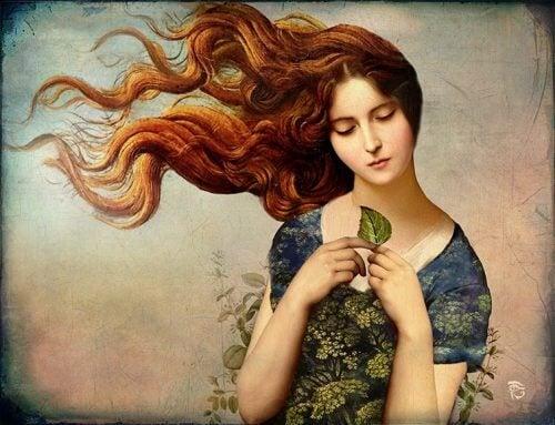 Frau mit Blatt und wehendem Haar denkt über Geheimnisse des Glücks nach
