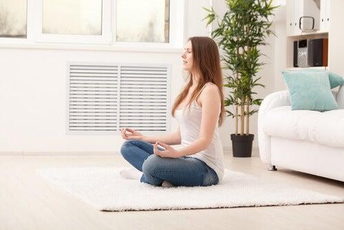Frau meditiert im Wohnzimmer, verbessere auch du damit dein Leben