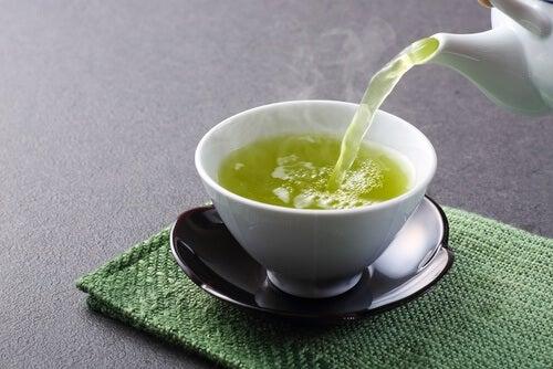 Zum Abnehmen mit grünem Tee gieße eine Tasse des heißen Getränks ein.