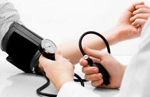 Ein Arzt misst den Blutdruck seines Patienten und empfiehlt die Eigenschaften von Kokoswasser.