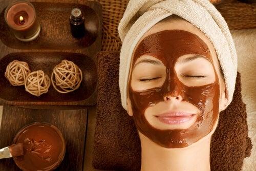 Eine entspannte Frau mit Gesichtsmaske gegen trockene Haut liegt mit geschlossenen Augen da.