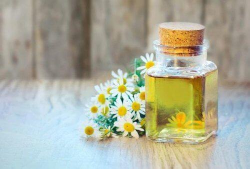 Flasche mit Öl und Kamillenblüten helfen gegen trockene Haut.